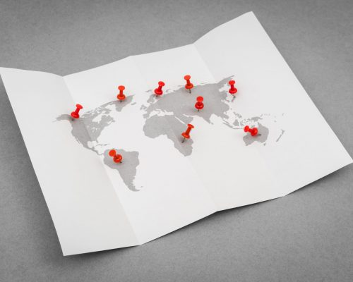 Paper folded world map  with red Pin Pointer
